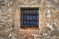 An old window in the castle with a rusty steel grate