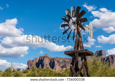An old windpump stands in front of Superstition Mountain in Apache Junction, Arizona.