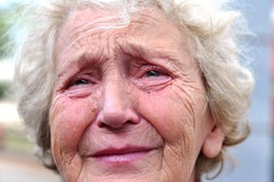 An old woman crying frantically. Tears in the eyes of an old wrinkled grandmother. Pain, disappointment, depression, loneliness, old age.