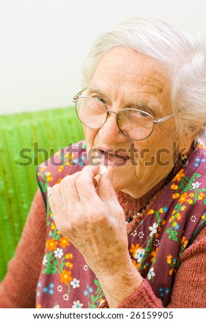 An old woman holding a pill in her hand, preparing to eat that - part of a series. - stock photo
