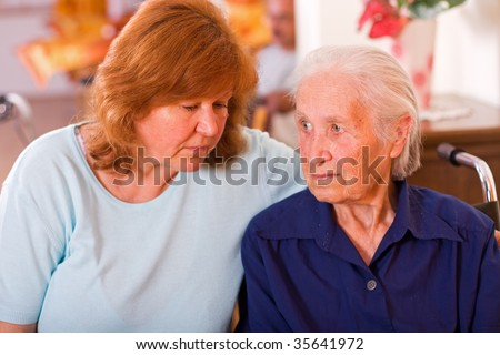 An old woman next to a mature one, a mother and a daughter, the elderly woman is sitting on a wheelchair having a worried facial expression.