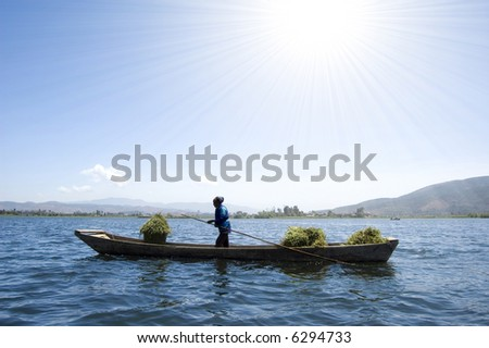 an old women carrying dry wheat by wooden boat after harvesting
