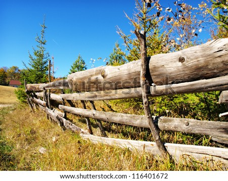 An old wood fence with a green country field behind it