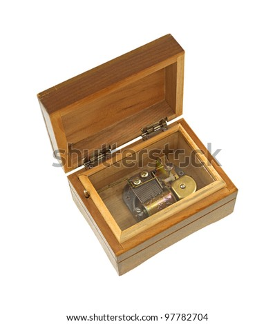 An old wood music box opened to show the mechanical workings through a glass top.