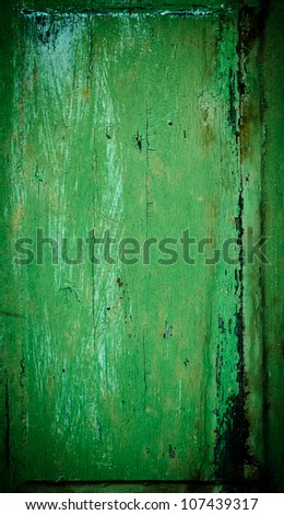 An old wood window panel with cracked green paint and grunge