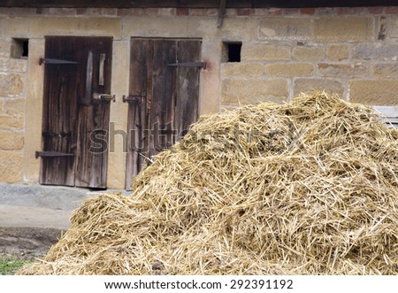 an old wooden barn door with a haystack in front of it