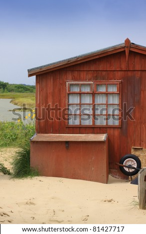 An old wooden beach hut set amongst sand dunes located at Christchurch in Dorset UK.