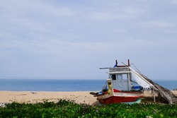 An old wooden boat moored on the beach