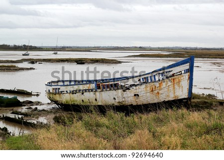 An old wooden boat resting on the sand on an estuary at low tide