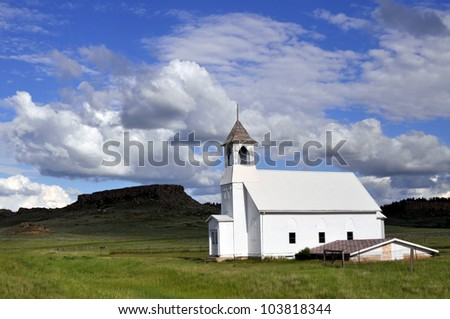 An old wooden church against a hill and grassland. Sunlight on the church, lifting it off the background. Shot in a remote rural area in Midwestern USA.
