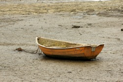 An old wooden dingy sits on a dry mud estuary in Raglan, New Zealand.