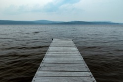An Old Wooden Dock Jutting Out Into A Dark And Gloomy Lake With Cold Water