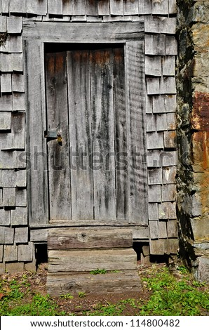 An old wooden door beside a chimney on the back of a house.
