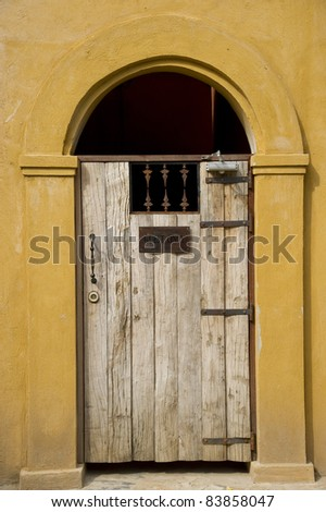 An old wooden door on yellow wall