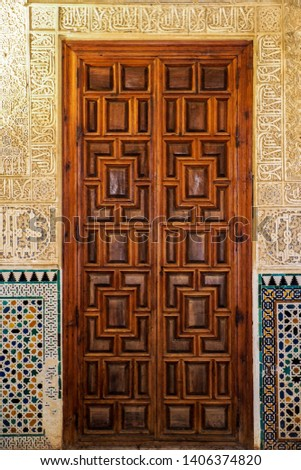 An old wooden door with an ancient Nasrid's pattern carving on stone wall  #1406374820