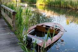 An old wooden fishing boat is moored to a pier on the river. Summer evening artistic landscape with a pond and reeds, selective focus.