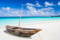 An old wooden fishing boat on a picturesque tropical beach