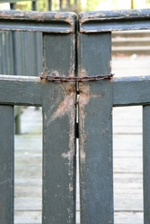 An old wooden gate closed with a chain