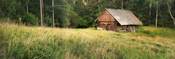 An old wooden house (hut, log cabin) on a green forest hill. Picturesque panoramic view. Idyllic rural scene. Travel, eco tourism. traditional architecture, summer vacations, past, history