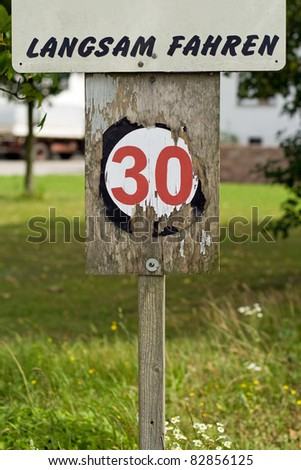 An old wooden 30 kilometers per hour speed limit sign
