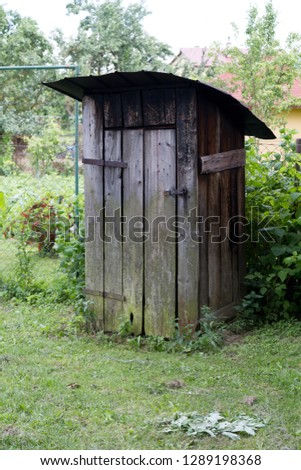 an old wooden outhouse (privy) in the garden in rural Slovakia