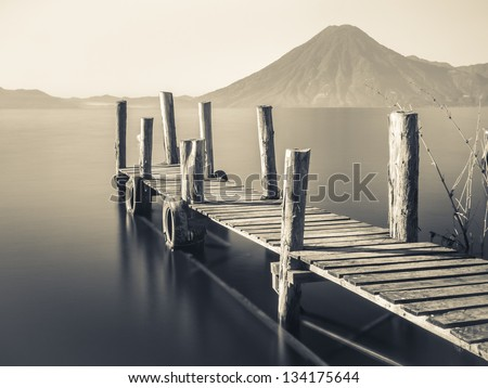 An old wooden pier juts out into lake Atitlan in Guatemala with volcano in background - long exposure