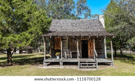 An old, wooden pioneer cabin, circled by trees, circa early 1900's, with a front porch, holding a rocking chair and a plant in a bucket. It has shake shingles, and a slate chimney.