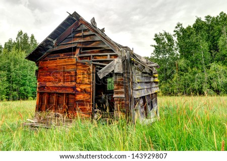 An old wooden shed in the middle of a field by the forest