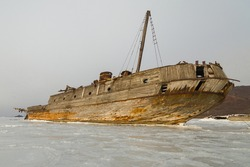 An old wooden Soviet whaling boat, the ship ran aground on the Bay shore, the front background is the sea shore, the background is the horizon with peninsulas, Vityaz Bay.