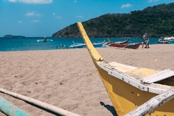 An old wooden traditional banca or outrigger boat lying in the sand dragged inland by the owner. At Calayo beach, Nasugbu, Batangas.