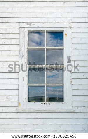 An old wooden window with eight panes of glass in an exterior wall of a white wood clapboard wall. There are reflections of blue sky and clouds in the glass. The wall is worn and paint is peeling. Stock photo ©