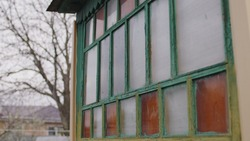 An old wooden window with multicolored panes. Multicolored glass panels on the antique window