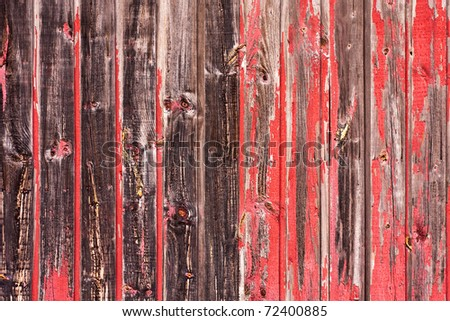 An old worn barn or antique wooden fence with chipped red paint.