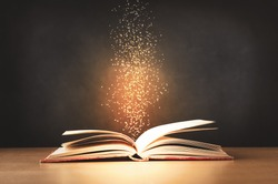 An old, worn, red text book, lying opened on a classroom desk with sparkles and stars rising upwards from its centre. Black chalkboard background.