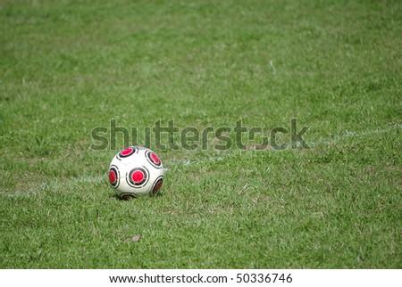 An old, worn soccer ball on a chalk line on a soccer field