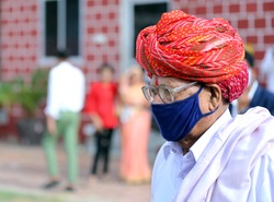 An old wrinkled indian rural man in red turban walking wearing mask. Protection from covid-19 pandemic. Indian rural traditional male dress now includes mask. Mask a latest fashion statement for old.