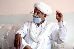 An old wrinkled indian rural man in white turban sitting wearing mask. Protection from covid-19 pandemic. Indian rural traditional male dress now includes mask. Mask a latest fashion statement for old