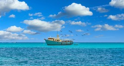 An old yellow and white fishing boat moored on aqua Caribbean water