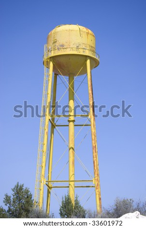 An old yellow water tower with graffiti against a blue sky.