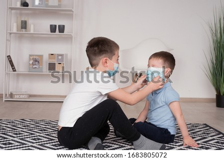 An older brother puts a medical protective mask on his younger brother. Caring for a little brother. Two funny brothers. Covid-19. Healthy childhood concept. Coronovirus protection. Home insulation.
