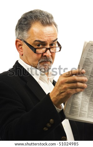 An older businessman with glasses holds up a newspaper.