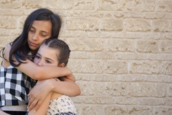 An older child hugs her sibling who is showing signs of sadness
