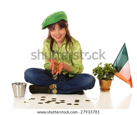 An older elementary girl dressed for St. Patrick's dropping handsful of gold coins and sitting beside a gold pot of Shamrocks with an Irish flag.