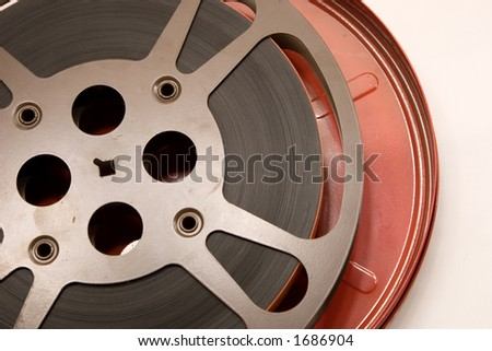An older film canister and film reel wrapped tightly and precisely.