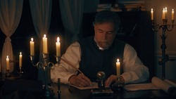 An older gentleman from the 18th century lit by candlelight sitting at his desk composing a letter using a quill pen and ink from a fancy ink well.
