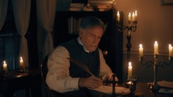 An older gentleman of the 18th century lit by candlelight composing a letter using a quill pen and ink from a fancy inkwell.