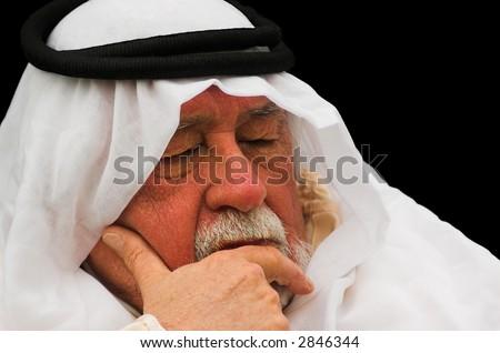 An older gentleman taking a nap, wearing Arabic headdress, a keffiyeh and agal.