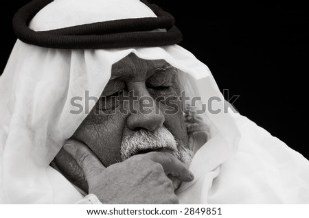 An older gentleman wearing Arabic headdress (a keffiyeh and agal), in contemplation.
