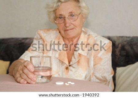 an older lady with a glas of water and tablet , focused on the glas and the tablet.