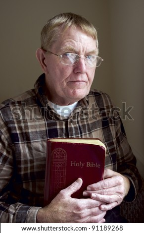 An older man holding his bible.